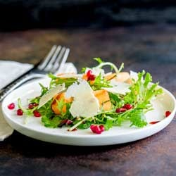 Square picture of melon and pomegranate salad on a shallow white plate.