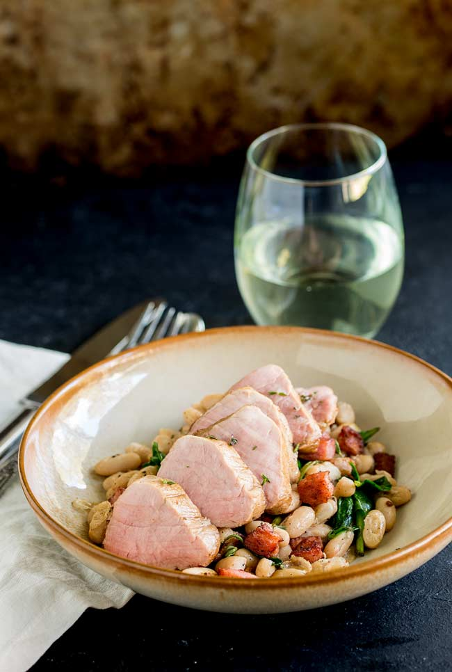 Full table view of a earthenware bowl, filled with white beans, crispy bacon and wilted spinach. Wine glass in the background.