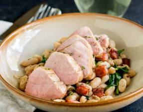 FEATURE IMAGE - Showing the whole dish of Pork tenderloin on top of a bowl of beans and bacon.