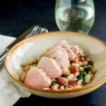 Succulent pork sat on a bed of creamy beans and crispy salty bacon. This Pork Tenderloin with Beans and Bacon delicious, comforting and oh so simple to make. Plus it looks elegant, which makes it perfect for entertaining. Recipe from Sprinkles and Sprouts | Delicious food for easy entertaining.