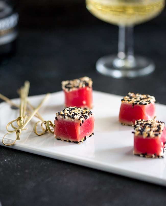 Close up of the seared sesame tuna cubes, on a white platter with champagne in the background.