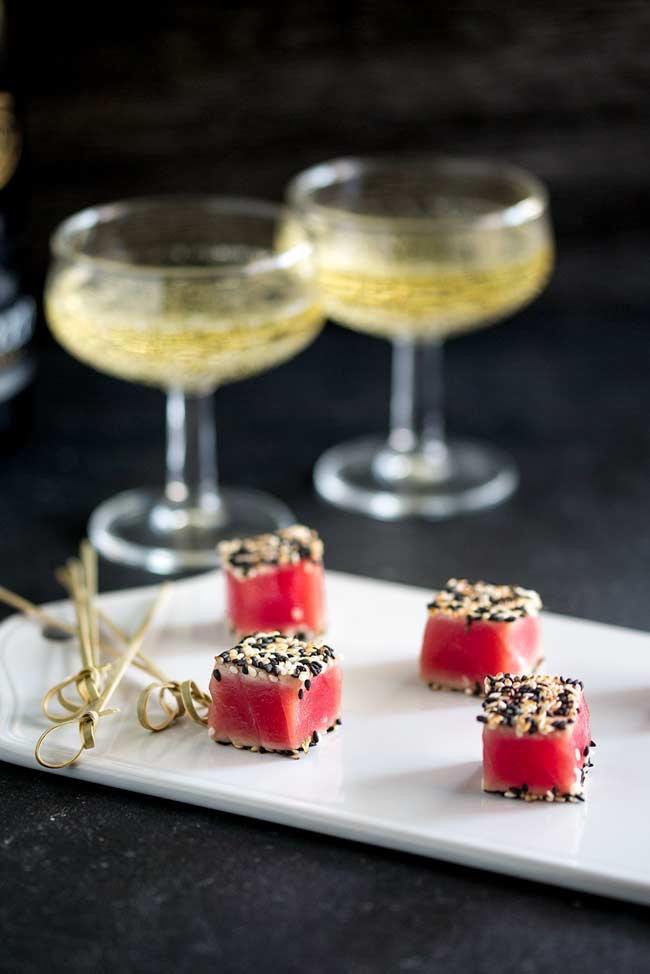 Full screen shot of the party platter. Seared Sesame Tuna Bites on a white platter, with skewers to serve and champagne served in coupe glasses.