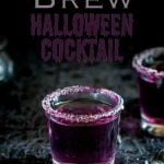 purple liquid in a small shot glass rimmed with sugar sat on a black halloween table