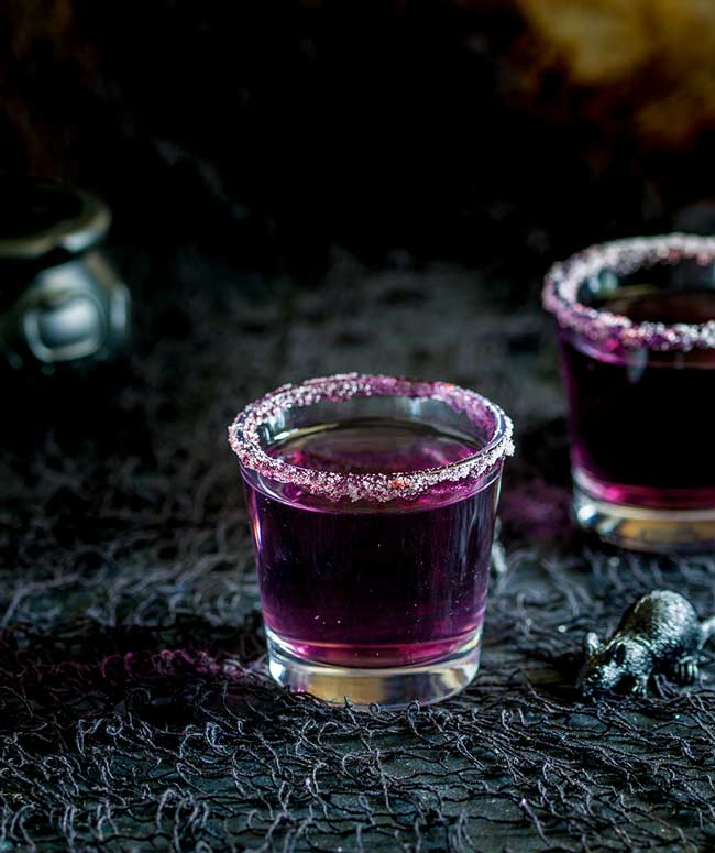 Bright purple cocktail in a sugar rimmed shot glass.