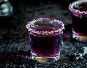 Single shot glass with a purple cocktail with a sugar rim.