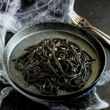 overhead showing the black pasta on a black plate with cobwebs over the table and cutlery