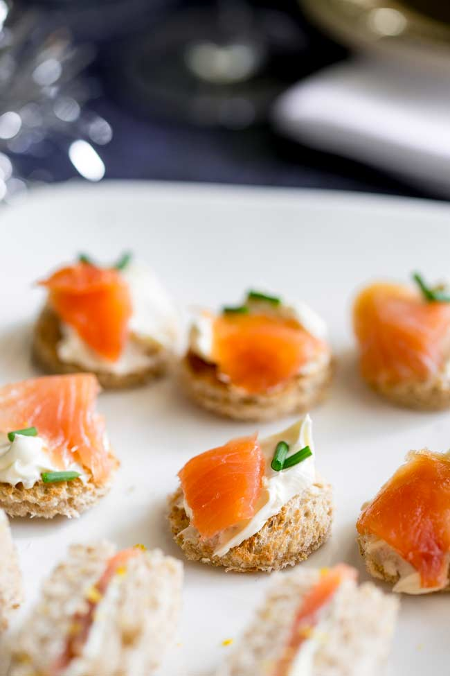 Round toasts spread with cream cheese and topped with smoked salmon and chives. On a white plate.