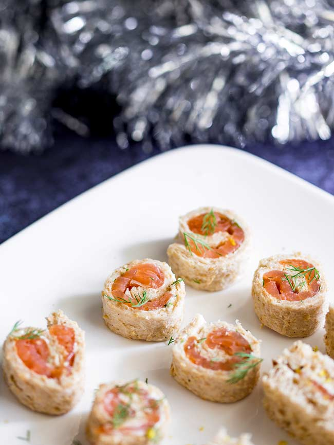Brown bread pinwheels with dill cream cheese and smoked salmon. Tinsel in the background.