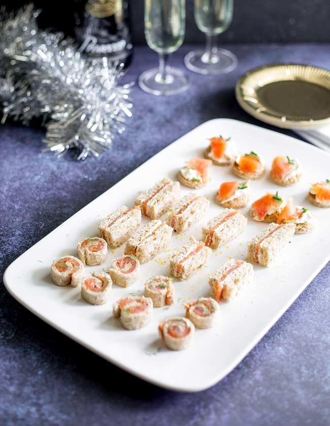 Overview of the smoked salmon appetizer platter on a purple/blue table with party plates and champagne in background