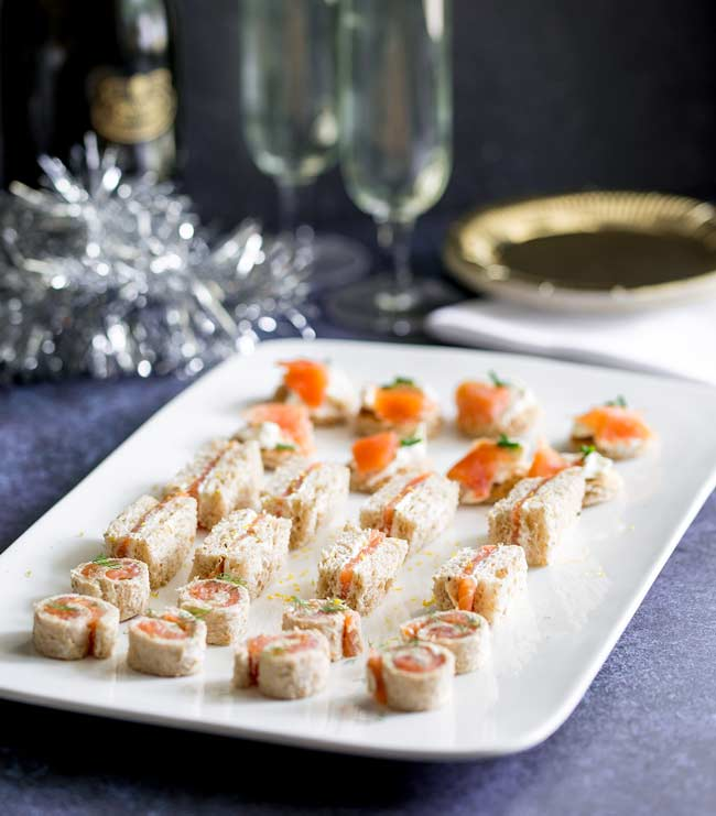 Purple/Blue Table, with gold plates, champagne flutes and tinsel. Large white platter with 3 different smoked salmon appetizers on it.