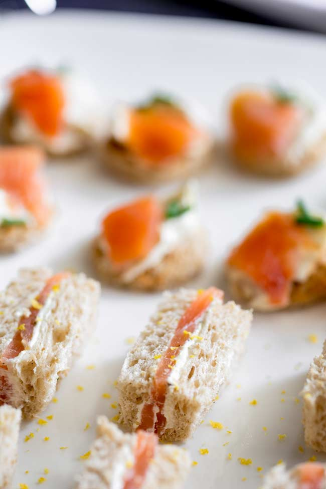 Brown bread with lemon cream cheese and and smoked salmon finger sandwiches on a large white plate. Pasta bites in the background.