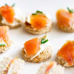 Toast rounds topped with cream cheese, chive and smoked salmon on a white plate.