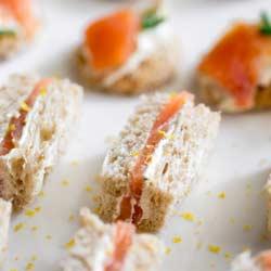 Smoked Salmon and Lemon Cream Cheese Sandwich bites on a white platter.