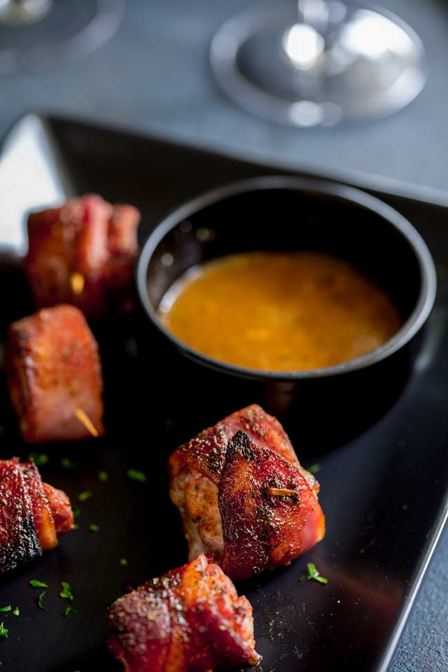 Close up on a Brown Sugar Bacon Wrapped Chicken Bites and a small black dish of mustard maple dipping sauce