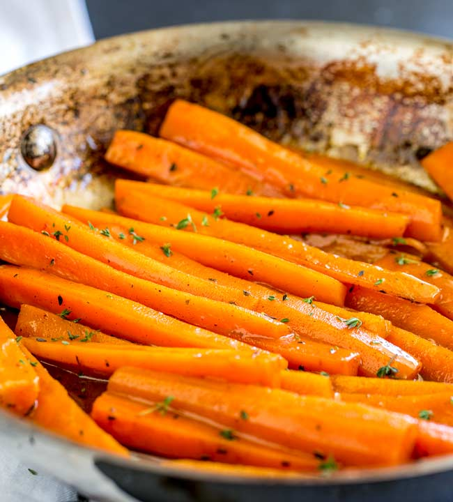 Close up on the Glazed carrots in a metal sauté pan.