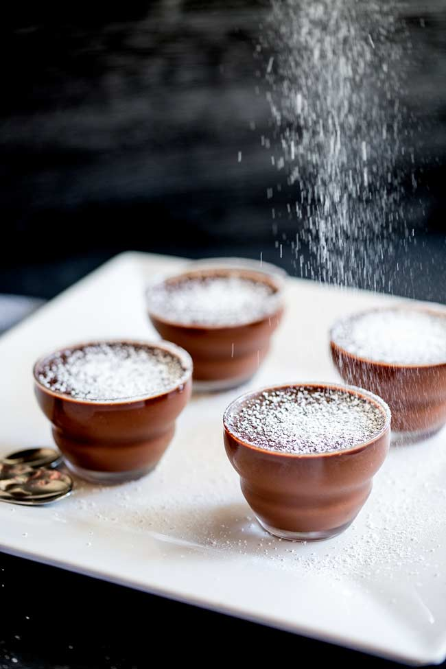 4 glass simple chocolate mousse pots on a white plate, with 4 spoons on the side and powdered sugar falling down.