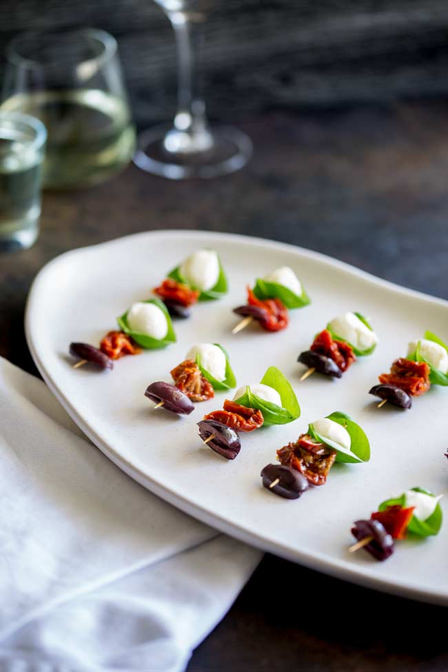 showing a rustic brown table with wine glasses in the background and a irregular white latter full of caprese style skewers