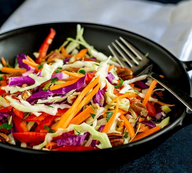 Red and white cabbage, red pepper and carrot slaw in a black bowl.