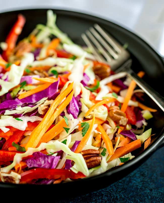 Large black bowl filled with winter slaw and a fork on the side.