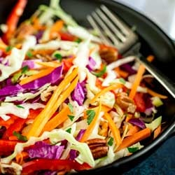 Square picture showing winter slaw in a black bowl.