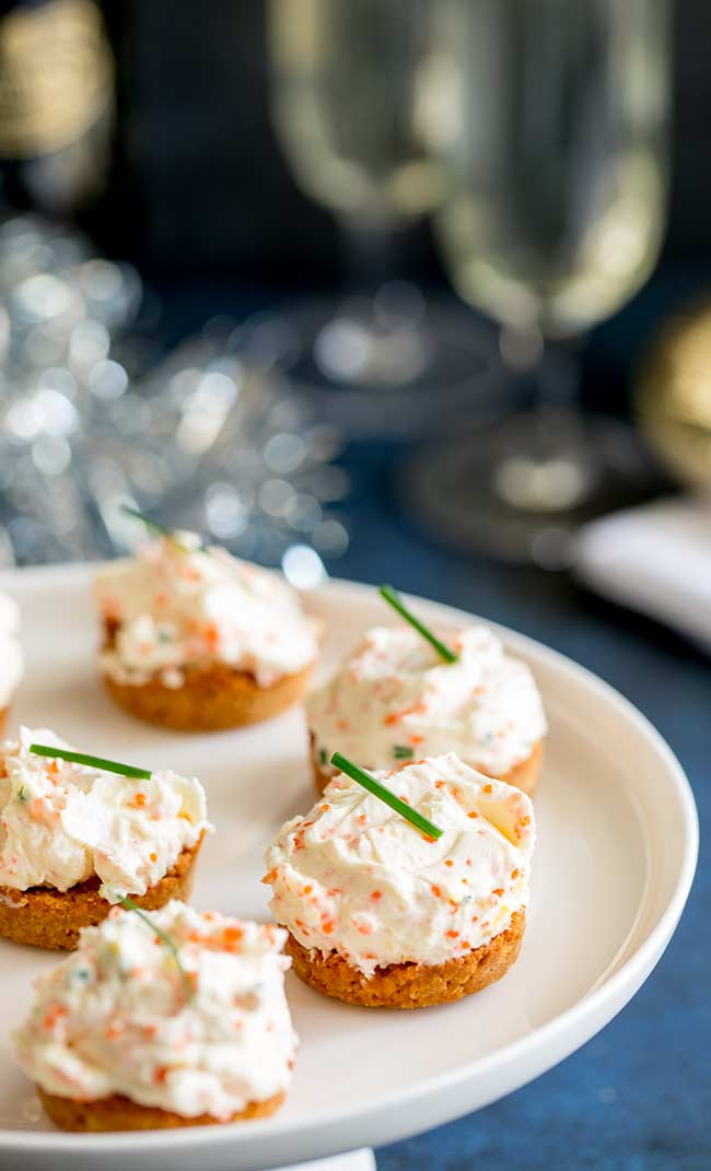 Savory cheesecakes garnished with chives on a white platter on a decorated table with tinsel and gold plates.