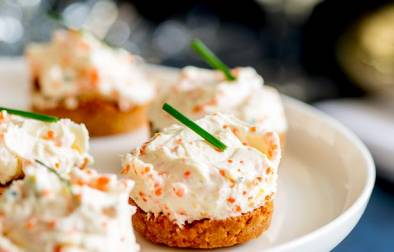 Close up on the savory cheesecake with a cracker base with cream cheese flacked with caviar and chives