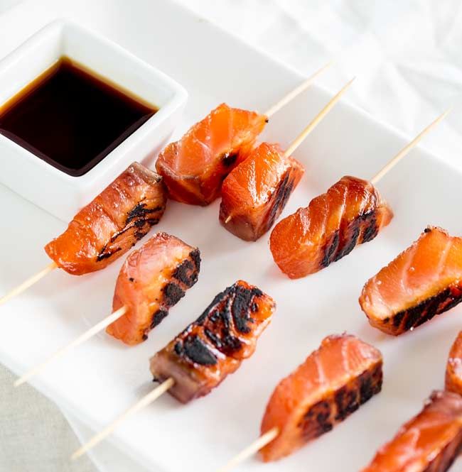 Overhead view showing the dark charred edge of the salmon skewers and soft cured inside.