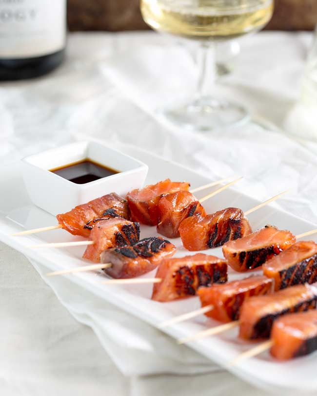 Long white platter, with cocktail stick skewered salmon bites, on a white table with champagne in the background.