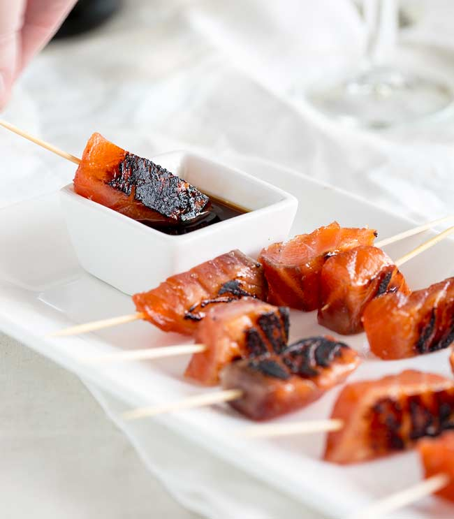 A brown sugar salmon skewers being dipped into a small white dish of soy sauce.