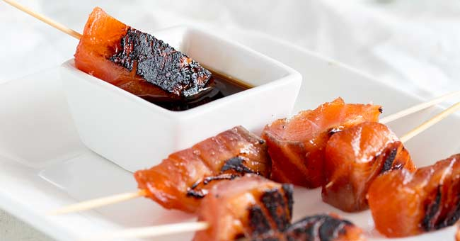 The cured Brown Sugar Salmon skewers being dipped into a white bowl of soy sauce.