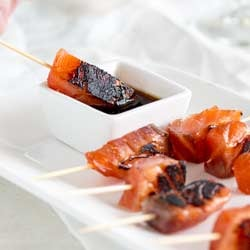 Square picture of brown sugar salmon skewer being dipped into soy sauce.