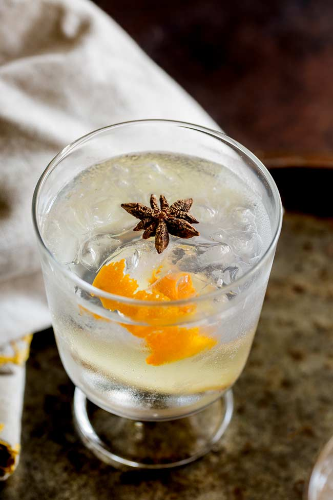 Overhead shot showing the star anise floating in the orange gin and tonic, with a linen napkin on an old metal tray