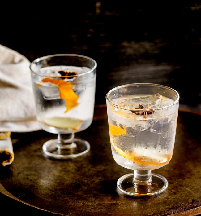 Two stemmed glasses with gin and tonic in them, garnished with star anise and orange zest. On an old metal tray with dark background
