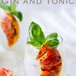 Long picture showing two glass of gin and tonic on a white table, scattered with ice