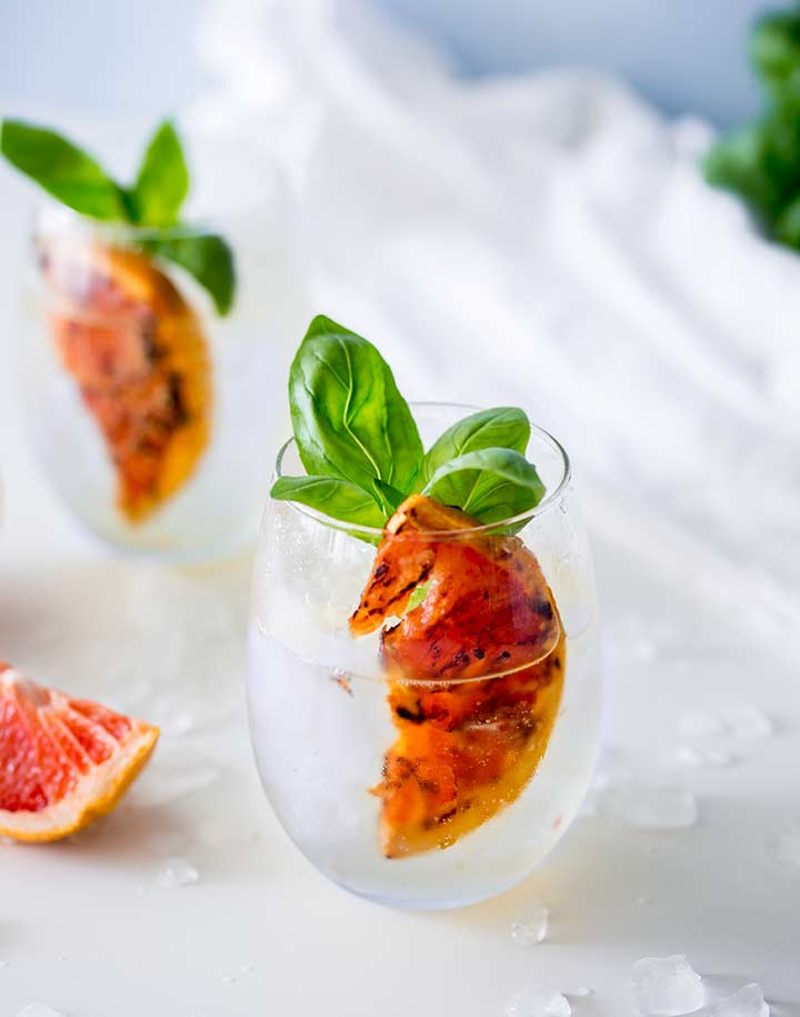 overhead view of white table with two stemless wineglass filled with a charred grapefruit wedge, basil leaves with gin and tonic