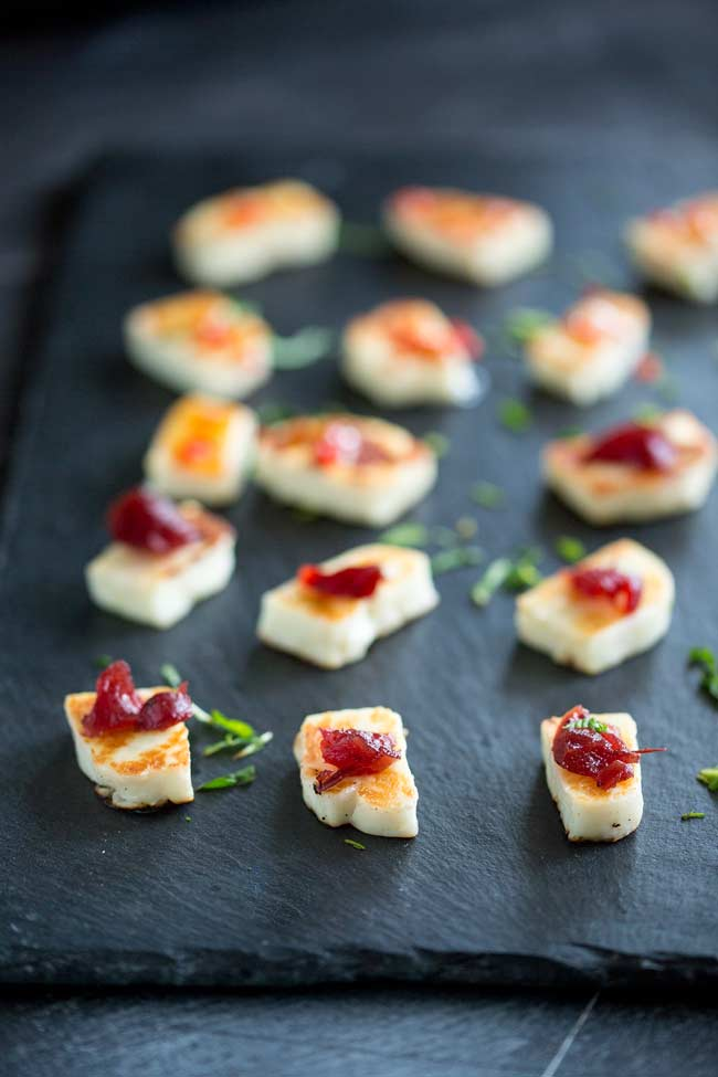 Golden grilled halloumi on a slate platter with a small dollop of red cranberry jelly on top.