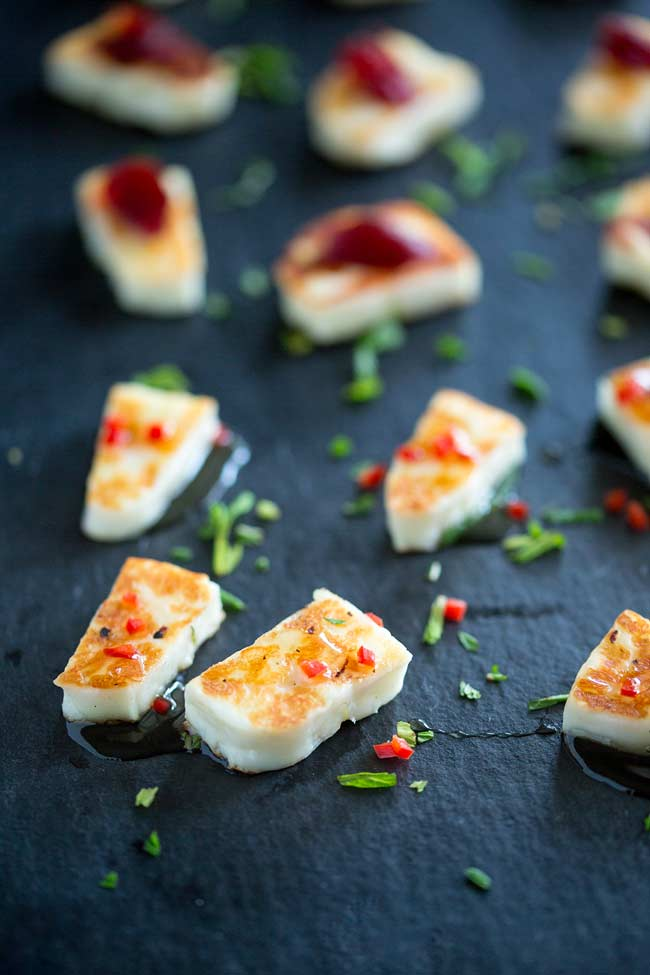 Close up of grilled halloumi cheese, speckled with red chilli and green mint.