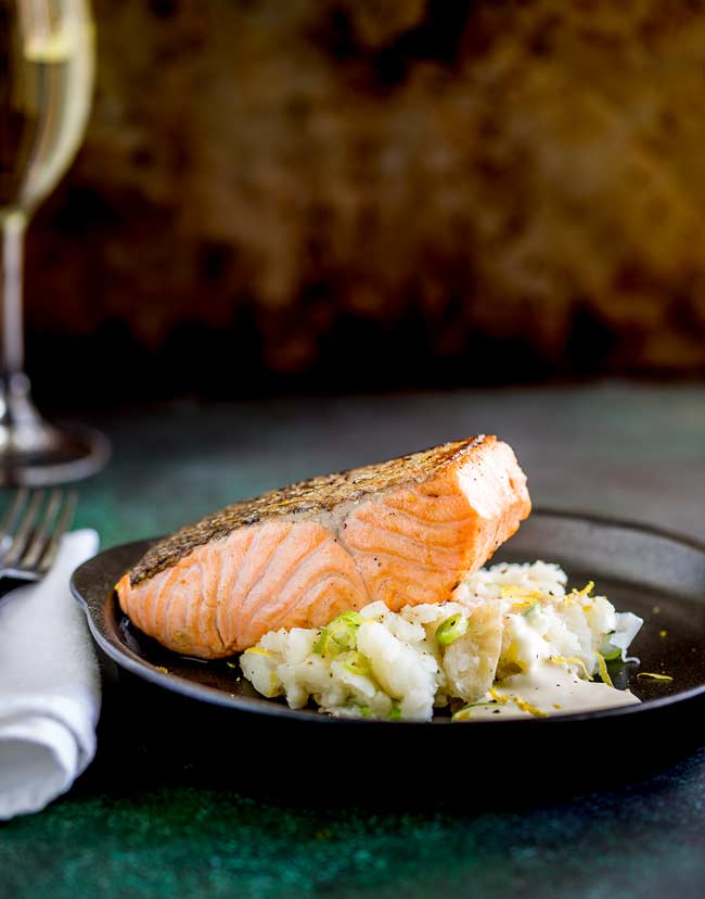 Black plate with a mound of smashed potatoes, a seared salmon fillet on top and a wine glass in the background.