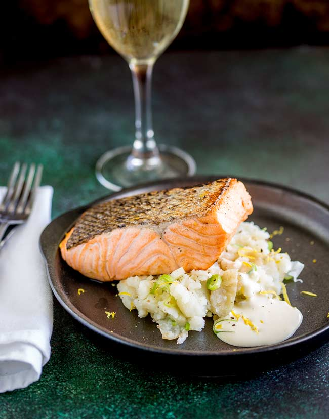 Table view, showing the plate of seared salmon and smashed potatoes, plus a wine glass and a white napkin with silver knife and fork.