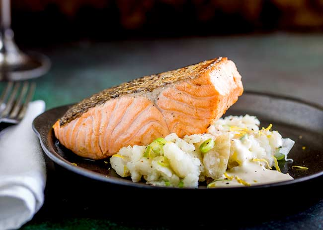 Close up on the pan seared salmon on a black plate.