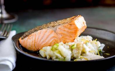 A juicy seared salmon fillet, sat on top of soft fluffy smashed potatoes, spiked with scallions and drizzled with horseradish cream. This Pan Seared Salmon with Creamy Smashed Potatoes is an elegant yet simple dinner party main course. Recipe by Sprinkles and Sprouts | Delicious food for easy entertaining.