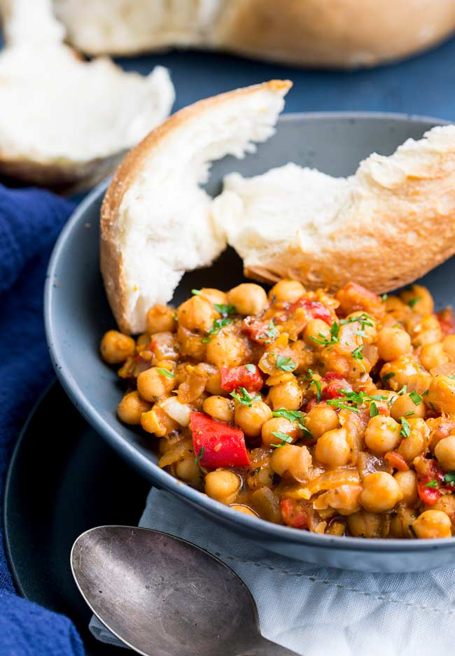 Close up of the chickpeas. Orange chickpea stew in a rustic grey bowl with crunch bread next to it.