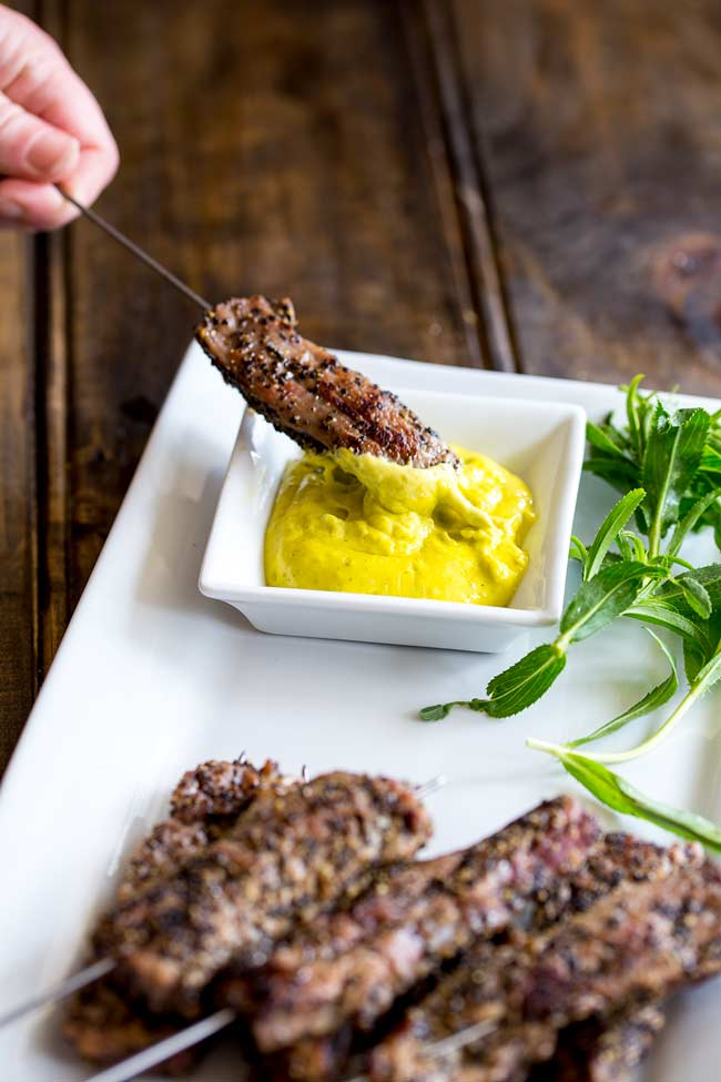 A pepper beef skewer being dipped into a small white pot of béarnaise sauce