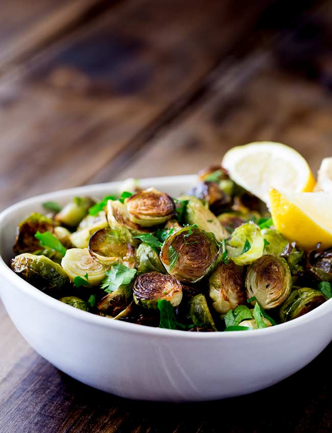 Serving bowl filled with roast brussel sprouts with lemon wedges in the background.