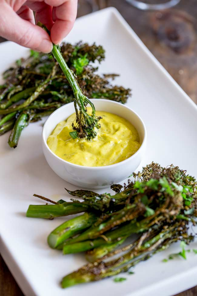Spear of roasted broccolini being dipped into a pot of Easy Béarnaise Sauce
