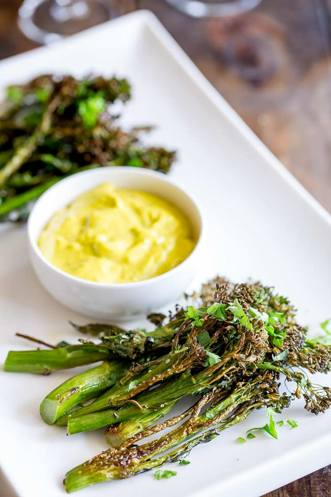 Long white platter with two stacks of roasted broccolini and a small bowl of béarnaise sauce.