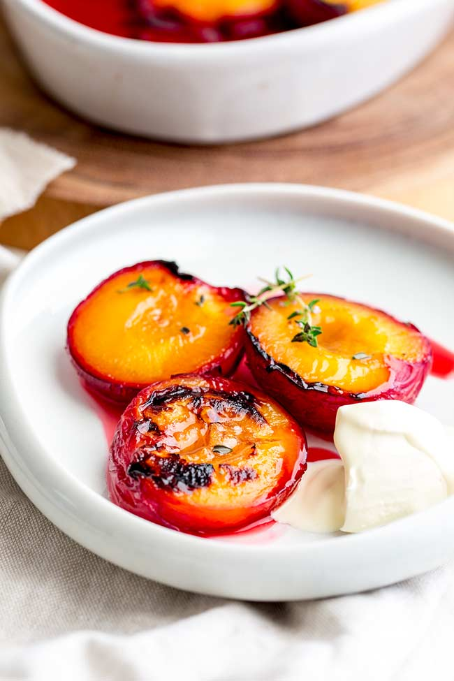 3 roasted plums on a heavily lipped white plate, garnished with a sprig of thyme and a dollop of cream.