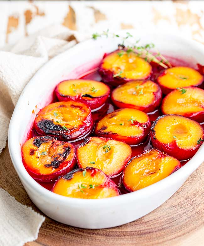White roasting dish filled with roasted plums and a bright red natural plum syrup.