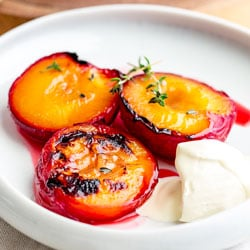Roasted Plums with Thyme and Brown Sugar | Tender roasted plums in a deliciously sweet and fragrant syrup. These Roasted Plums are the perfect simple dessert. Served with fresh cream or vanilla ice cream they are delicious and so beautiful.  Recipe by Sprinkles and Sprouts | Delicious Food for Easy Entertaining #fruitdessert #easy #roastedfruit #dessert