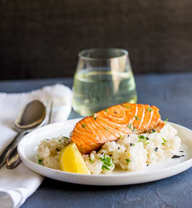 Blue table with white plate of lemon risotto and seared salmon, small wine glass in background